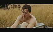 Bum driller Casey Affleck in tin bath in a field